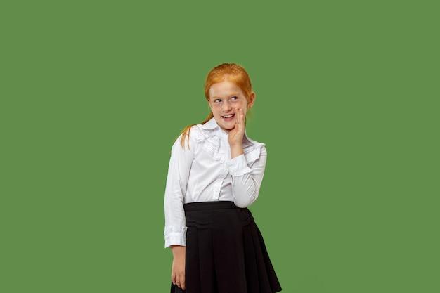 Segreto, concetto di gossip. ragazza che bisbiglia un segreto dietro la sua mano. ha isolato su sfondo verde alla moda per studio. giovane adolescente emotivo. emozioni umane, concetto di espressione facciale. Foto Gratuite