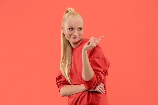 Segreto, concetto di gossip. giovane donna che bisbiglia un segreto dietro la sua mano. donna d'affari isolata su sfondo corallo alla moda per studio. giovane donna emotiva. emozioni umane, concetto di espressione facciale. Foto Gratuite