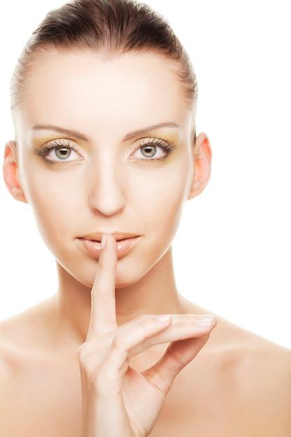 秘密-彼女の口の上の彼女の指を持つ少女 Premium写真