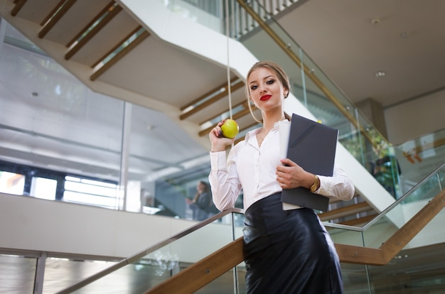 Secretary with papers and an apple in her hands goes for lunch on the stairs in the office. business woman concept Premium Photo