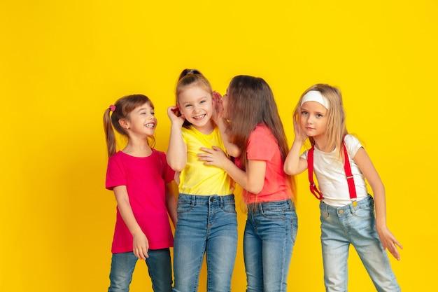 Segreti. bambini felici che giocano e si divertono insieme su sfondo giallo studio. i bambini caucasici in abiti luminosi sembrano giocosi, ridenti, sorridenti. concetto di educazione, infanzia, emozioni. Foto Gratuite