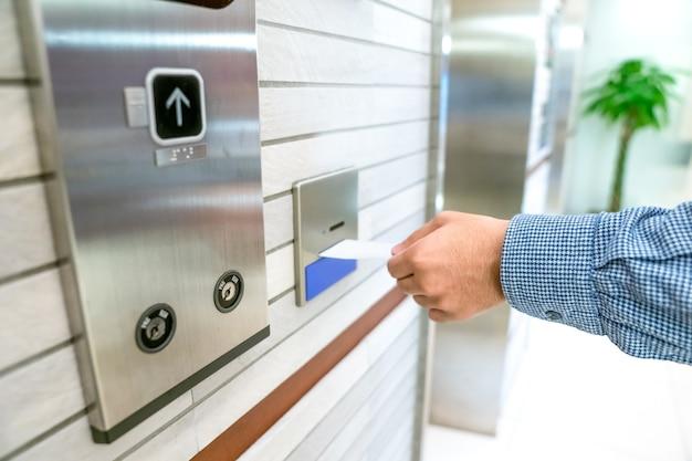 리프트 또는 엘리베이터 액세스 제어를 확보하고, 사람의 손에 키 카드를 올려 놓고 엘리베이터 문을 잠금 해제하기 위해 카드 홀드에 삽입합니다. 프리미엄 사진