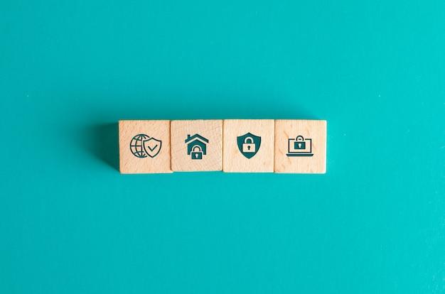 ターコイズブルーのテーブルフラットに木製のブロックのアイコンとセキュリティの概念を置きます。 無料写真