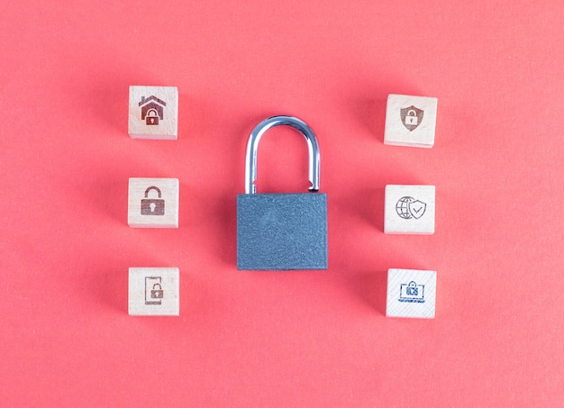 Security concept with lock, icons on wooden cubes on pink table flat lay. Free Photo