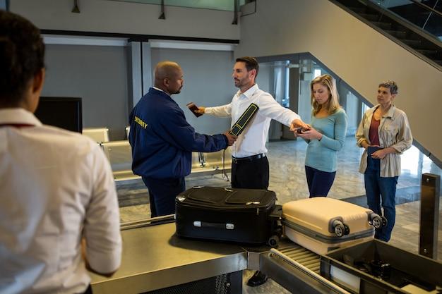 La guardia di sicurezza perquisisce i passeggeri in coda Foto Gratuite