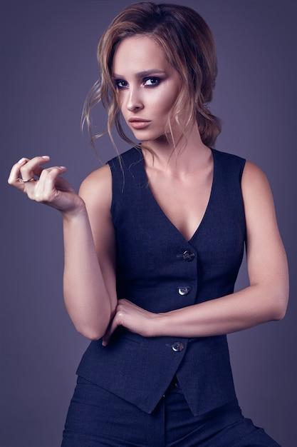 Seductive blonde girl in pants and a man's waistcoat Premium Photo