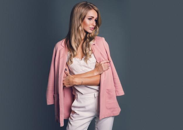 Соблазнительная блондинка в розовой куртке позирует Бесплатные Фотографии