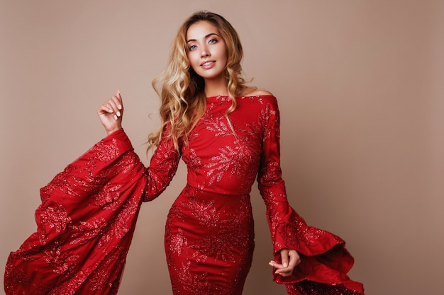 Seductive blonde woman posing in luxury red dress with wide sleeves. fashionable look. blond wavy hairs. Free Photo