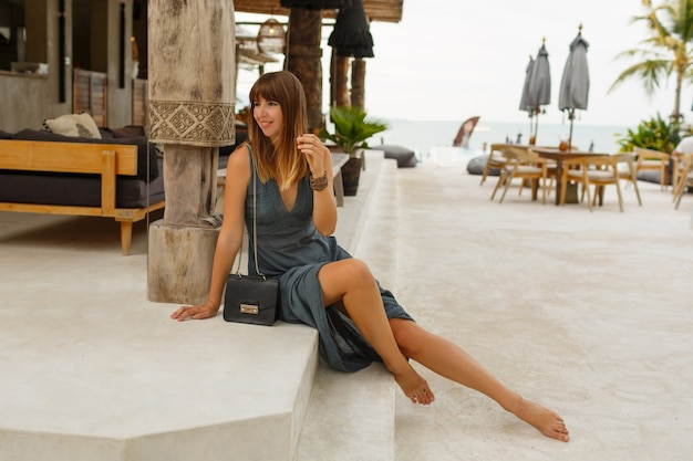 Seductive brunette female in sexy dress posing in stylish  beach restaurant in  asian style. Free Photo