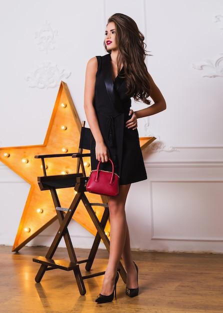 우아한 검은 드레스와 놀라운 보석 포즈의 매혹적인 유행 여자 무료 사진