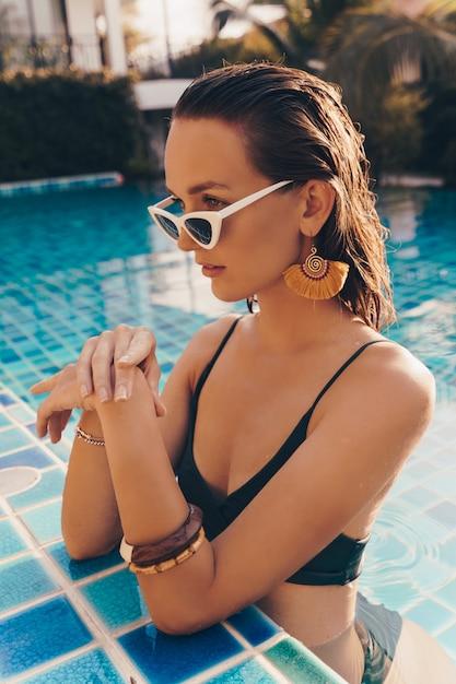 Donna graziosa seducente in orecchini gialli alla moda con l'ente perfetto che posa nello stagno durante le vacanze sulla località di soggiorno di lusso Foto Gratuite