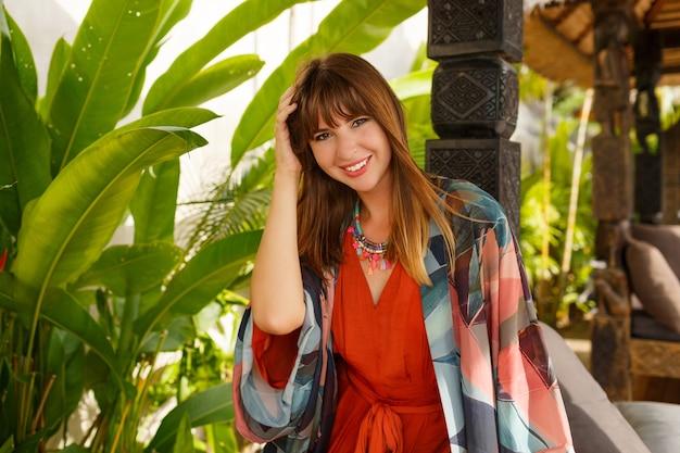トロピカルラグジュアリーリゾートでポーズをとる自由奔放な夏服で魅惑的なスタイリッシュな女性。休暇の概念。 無料写真