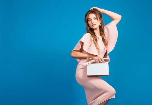 핑크 명품 드레스, 여름 패션 트렌드, 세련된 스타일, 블루 스튜디오 배경, 유행 핸드백을 들고 매혹적인 젊은 세련된 섹시한 여자 무료 사진