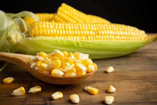 Seeds and sweet corn on wooden table. Free Photo