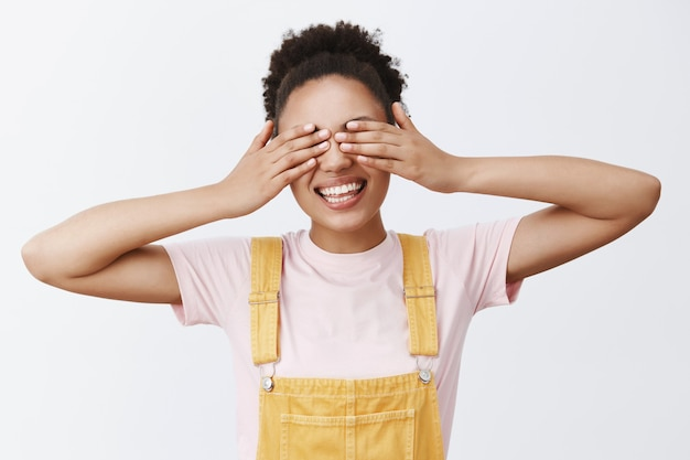 Not seeing problems, let me know when come out. portrait of charming and carefree african american in yellow overalls, closing eyes with palms and smiling broadly, waiting for surprise gift Free Photo