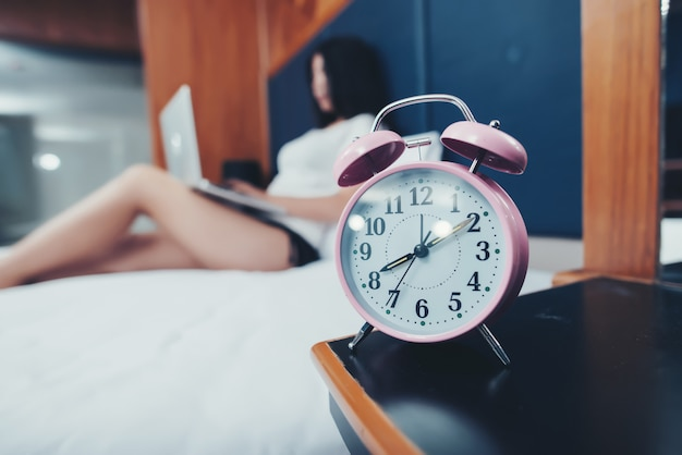 Select focus clock with beautiful woman working on bed Free Photo