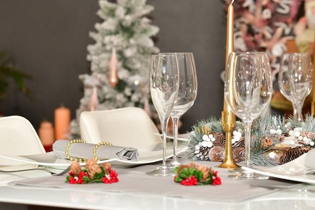 Seleziona il punto focale di un tavolo con bicchieri, una ghirlanda di pigna e altre decorazioni natalizie Foto Gratuite