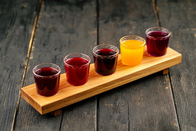검은 나무 배경에 다른 천연 과일 알코올 팅크 샷 선택 프리미엄 사진