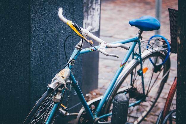壁の近くに駐車した青い自転車の選択的なクローズアップショット 無料写真
