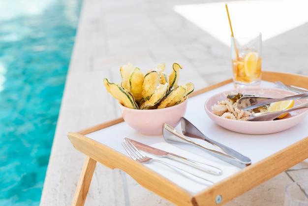 Селективный снимок крупным планом деревянного подноса, наполненного едой, серебром и стаканом Бесплатные Фотографии