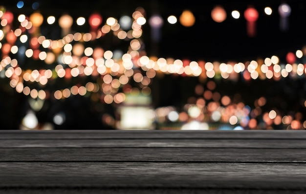 Selective empty wooden table in front of abstract blurred festive light background with light spots and bokeh Premium Photo