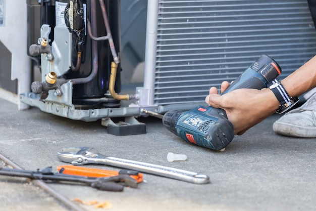 Selective focus air conditioning repair, technician man hands using a screwdriver fixing modern air conditioning system Premium Photo