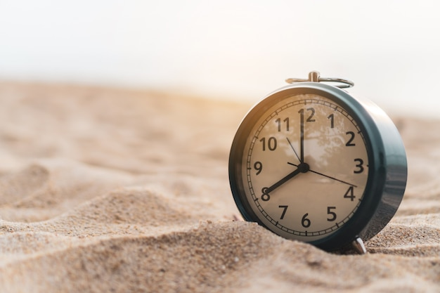 Selective focus of alarm clock with nature background. Premium Photo