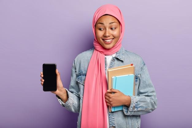 Селективный фокус. очаровательная жизнерадостная женщина с темной кожей носит на голове шелковый розовый шарф Бесплатные Фотографии