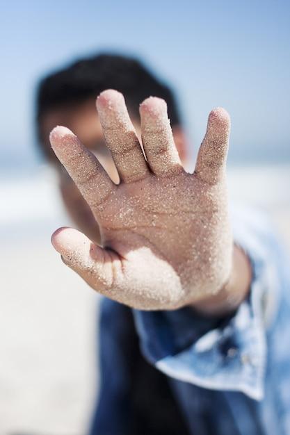 ビーチで彼の顔を覆っている男性の砂浜の手のひらのセレクティブフォーカスクローズアップショット 無料写真
