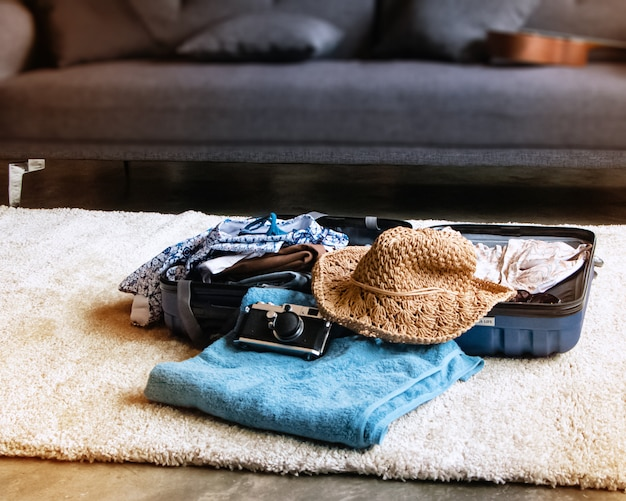 In selective focus of cloths,bath towel,hat and camera.the accessories for holiday trip,put on ground floor,beside for packking,blurry light around Premium Photo