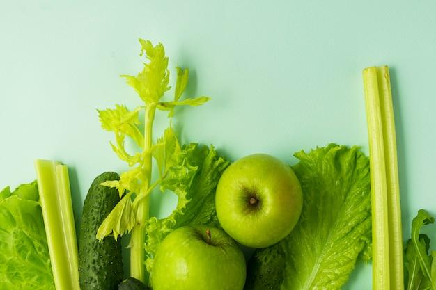 Селективный фокус, детокс-питание, зеленая диета на овощах и фруктах. натуральные продукты на синем фоне Premium Фотографии