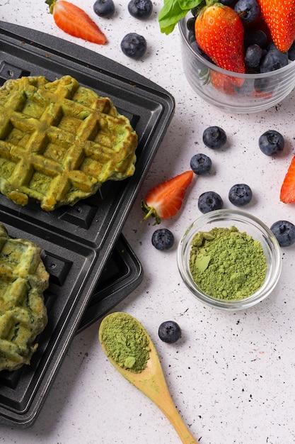 Выборочный фокус, зеленые творожные вафли с матча и свежие ягоды на светлом фоне Premium Фотографии