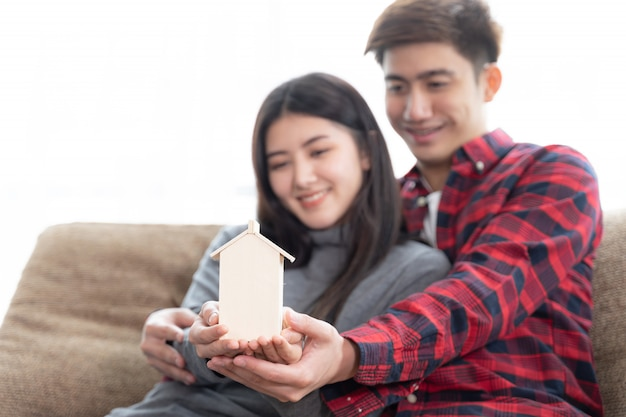 Selective focus at hand's young couple holding mini wooden house on the sofa in bedroom Free Photo