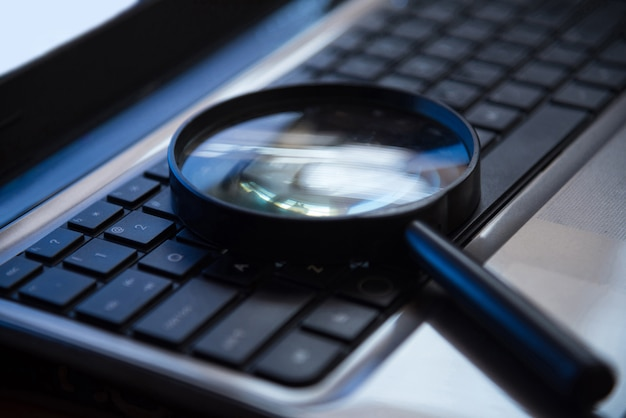 Selective focus on keyboard with magnifier searching concept Premium Photo