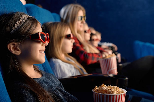 Messa a fuoco selettiva del bambino che ride con gli occhiali 3d, mangiare popcorn e guardare film divertenti. bambina sveglia che gode del tempo con gli amici nel cinema Foto Gratuite