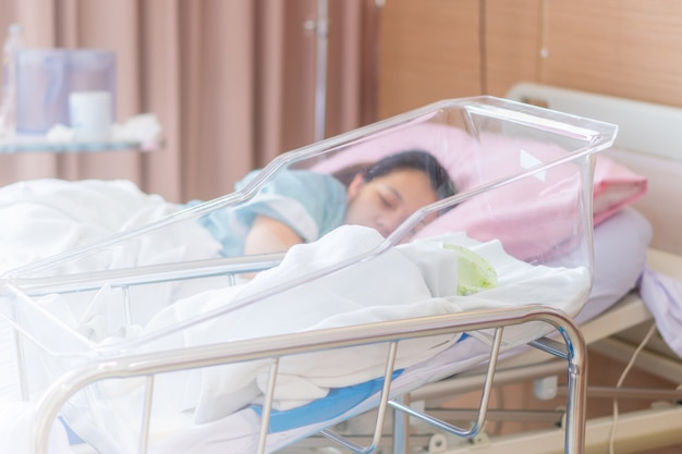 Selective focus of newborn baby boy and new mother sleeping in a hospital Premium Photo