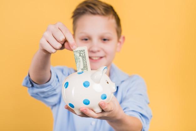 노란색 배경 폴카 도트 세라믹 돼지 저금통에 통화 메모를 삽입하는 소년의 선택적 초점 무료 사진