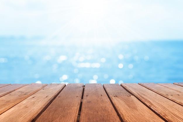 Селективный фокус старой деревянной таблицы с красивой предпосылкой пляжа для дисплея вашего продукта. Premium Фотографии