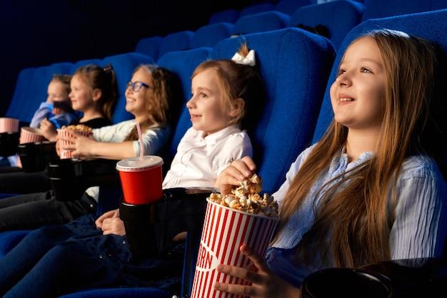 映画館で快適な椅子に笑っている友達と座っているポップコーンバケツを持って笑顔の少女の選択と集中。漫画や映画を見たり、時間を楽しんでいる子供たち 無料写真