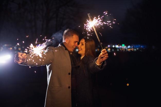 屋外で休日の時間を楽しんでいる若いカップルの手に線香花火の選択的な焦点。 Premium写真