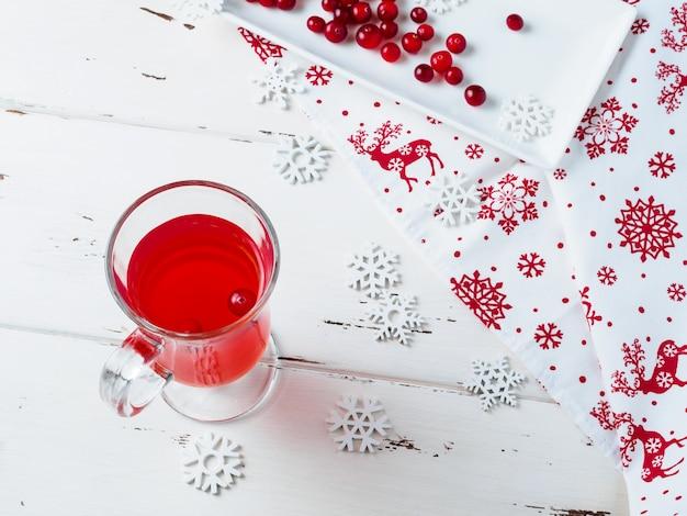 유리 컵에 신선한 음료에 크랜베리에 선택적 초점. 흰색 직사각형 세라믹 접시에 딸기, 새해 장식이 달린 냅킨 및 테이블에 눈송이. 프리미엄 사진