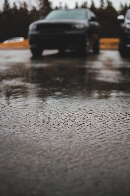 Selective focus photo of vehicle parked on concrete pavement Free Photo
