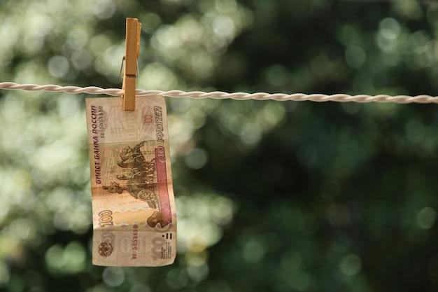 Colpo di messa a fuoco selettiva di una banconota appesa a un filo con una molletta Foto Gratuite
