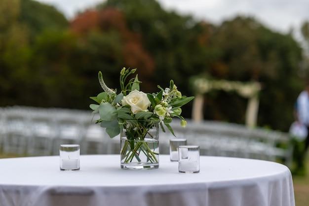Messa a fuoco selettiva colpo di bellissimi fiori in un vaso su un tavolo a una cerimonia di matrimonio Foto Gratuite