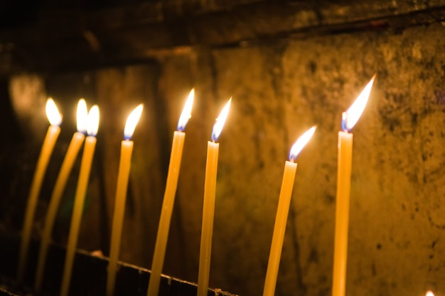 Selective focus shot of burning yellow candles inside the church Free Photo