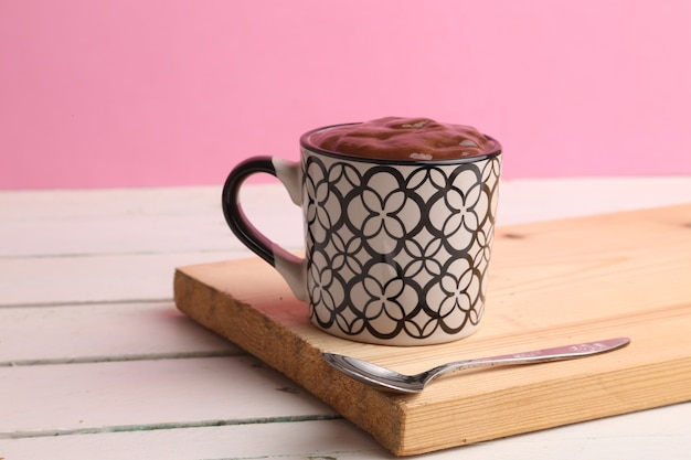 Selective focus shot of a cup of hot chocolate on a wooden board with a pink background Free Photo