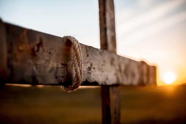 Colpo di messa a fuoco selettiva di una mano fatta una croce di legno con la corda avvolta e sfondo sfocato Foto Gratuite
