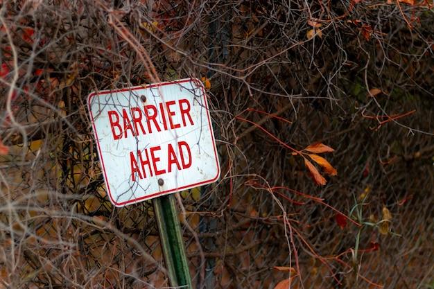 金属フェンスに寄りかかった標識前方標識の選択的フォーカスショット 無料写真