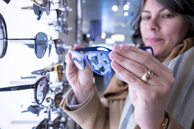 파란색 선글라스를 들고 여성의 선택적 초점 샷 무료 사진