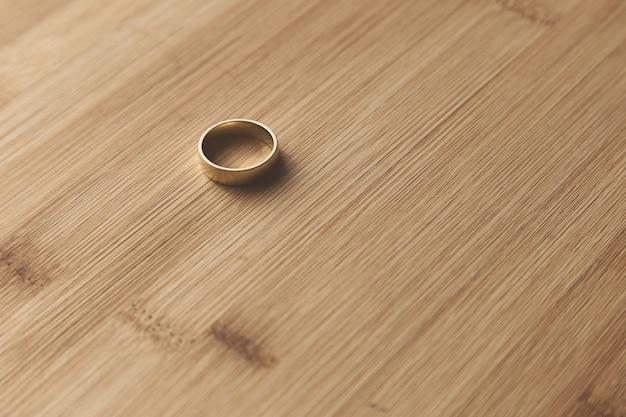 木製の表面に金の結婚指輪のセレクティブフォーカスショット 無料写真